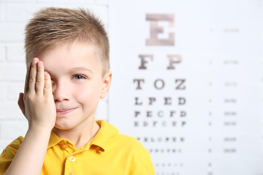 A little boy standing in front of a letter chart, covering one eye and smiling