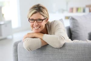 A smiling elderly lady wearing glasses while sitting on a couch