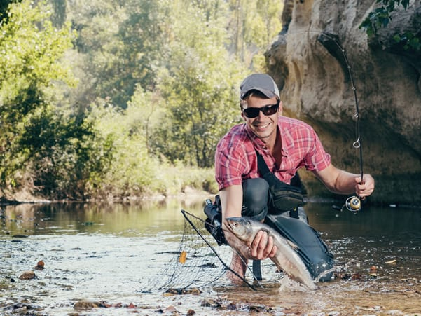 A smiling man wearing sunglasses and holding a freshly caught fish