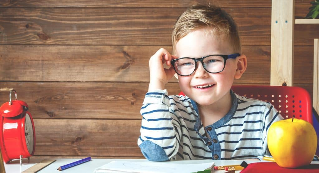Happy child wearing glasses doing his homework